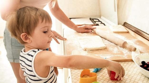Portret van een jonge, mooie vrouw die haar kleine kind leert om koekjes te maken en taarten te bakken in de keuken thuis