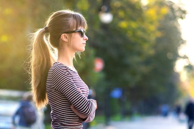 Portret van een jonge mooie vrouw die in de warme herfstdag buiten op straat in de stad staat