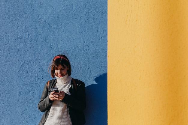 Portret van een jonge mooie vrouw die in openlucht mobiele telefoon over blauwe en gele achtergrond met behulp van
