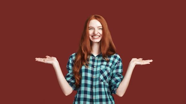 Portret van een jonge mooie vrouw die jongleert met de handpositie voor het gooien van voorwerpen, kijkend naar de camera met een glimlach, geïsoleerd op rode achtergrond