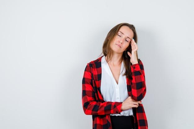 Portret van een jonge, mooie vrouw die lijdt aan hoofdpijn in een casual outfit en er pijnlijk vooraanzicht uitziet