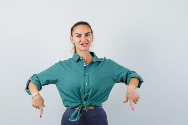 Portret van een jonge, mooie vrouw die naar beneden wijst in een groen shirt en er vrolijk vooraanzicht uitziet
