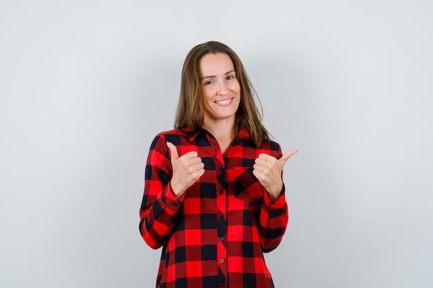 Portret van een jonge, mooie vrouw die naar tegenovergestelde richtingen wijst in een casual shirt en er vrolijk vooraanzicht uitziet