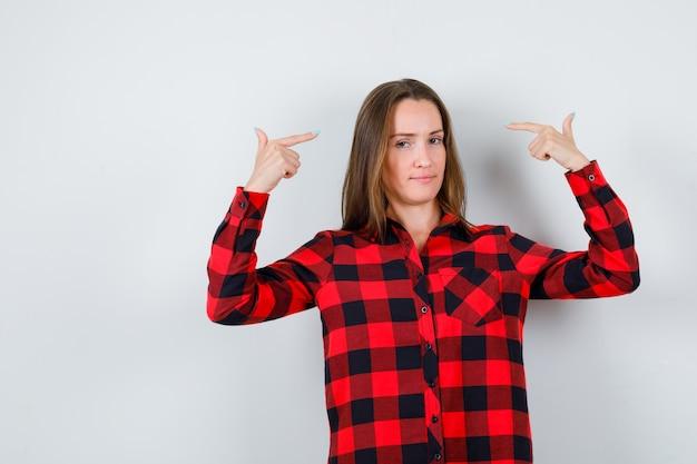 Portret van een jonge, mooie vrouw die naar zichzelf wijst in een casual shirt en er ongezellig uitziet