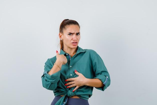Portret van een jonge, mooie vrouw die naar zichzelf wijst terwijl ze de hand op de borst houdt in een groen shirt en er verbijsterd vooraanzicht uitziet