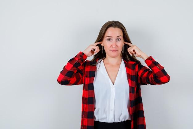 Portret van een jonge, mooie vrouw die oren stopt met vingers in een casual outfit en er ongezellig uitziet