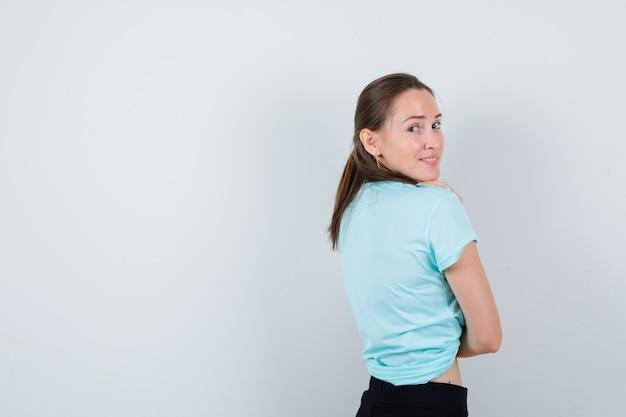 Portret van een jonge, mooie vrouw die over de schouder in een t-shirt kijkt en er vrolijk uitziet