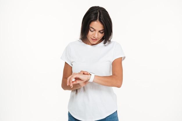 Portret van een jonge mooie vrouw die slim horloge bekijkt