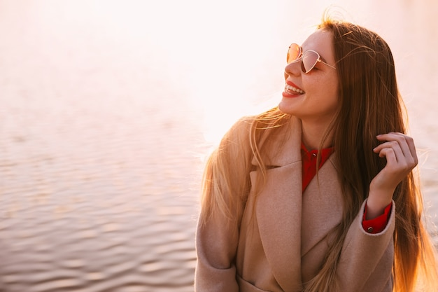 Portret van een jonge mooie vrouw die van zonsondergang aan meer geniet. warme zonsondergangkleuren.
