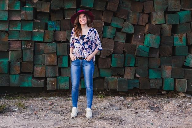 Portret van een jonge mooie vrouw die vrijetijdskleding en een moderne hoed draagt, zich over groene houtsneden bevindt en glimlacht. buitenshuis levensstijl.