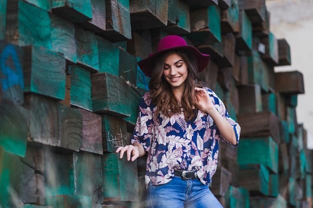 Portret van een jonge mooie vrouw die vrijetijdskleding en een moderne hoed draagt, zich over groene houtsnedenachtergrond bevindt en glimlacht. buitenshuis levensstijl.