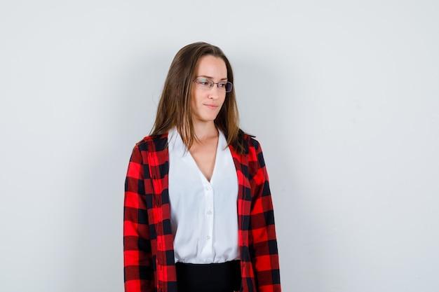 Portret van een jonge, mooie vrouw die wegkijkt in een casual outfit en er ongezellig uitziet