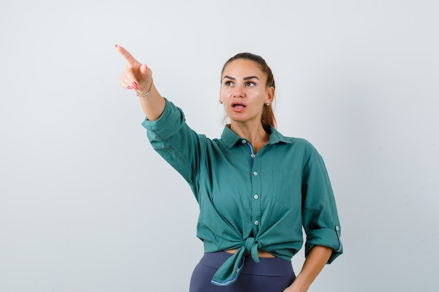Portret van een jonge, mooie vrouw die wegwijst in een groen shirt en er verbijsterd vooraanzicht uitziet