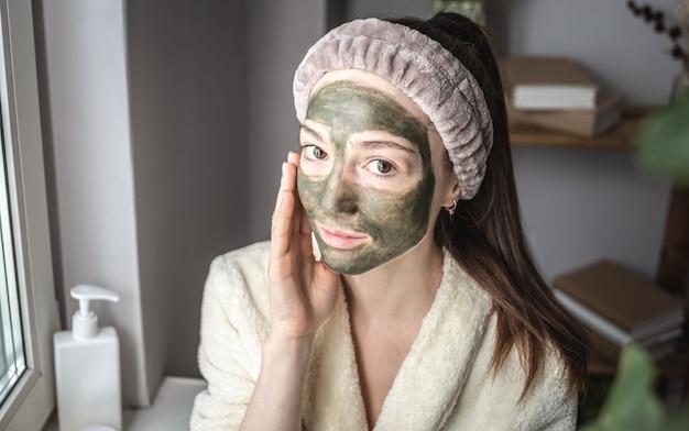 Portret van een jonge mooie vrouw in een badjas en met een cosmetisch groen masker op haar gezicht
