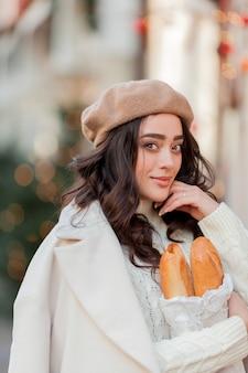Portret van een jonge mooie vrouw in een baret in een europese stad. jonge vrouw houdt een papieren zak met stokbrood. kerstmis. vakantie.