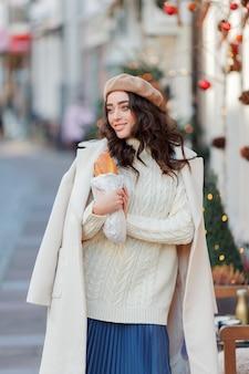 Portret van een jonge mooie vrouw in een baret in een europese stad. jonge vrouw houdt een papieren zak met stokbrood. kerstmis. vakantie. Premium Foto