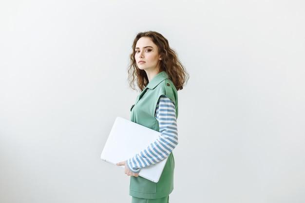 Portret van een jonge mooie vrouw in een groen pak met een laptop op een witte scène in de studio