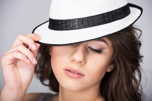 Portret van een jonge mooie vrouw in een hoed.