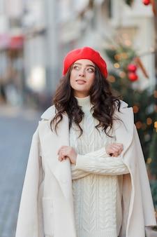Portret van een jonge mooie vrouw in een rode baret in een europese stad. jonge vrouw houdt een papieren zak met stokbrood. kerstmis. vakantie. Premium Foto