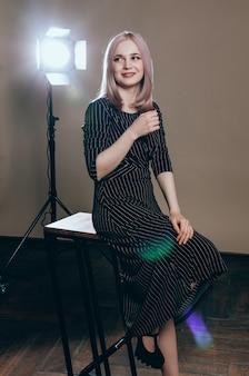 Portret van een jonge mooie vrouw in het licht flitst. mooie blondevrouw in zwarte kleding