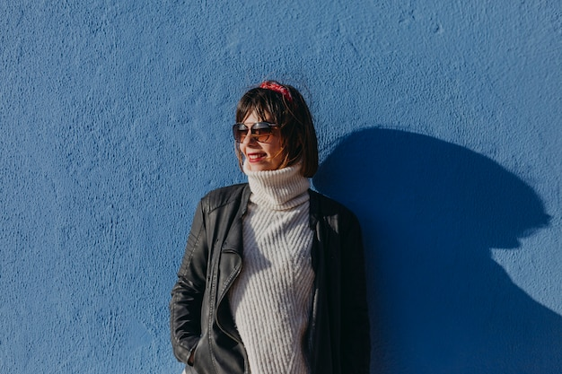Portret van een jonge mooie vrouw in openlucht over blauwe achtergrond