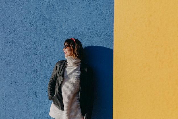 Portret van een jonge mooie vrouw in openlucht over blauwe en gele achtergrond
