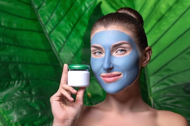 Portret van een jonge mooie vrouw met een gezonde gladde huid houdt een potje cosmetische producten.
