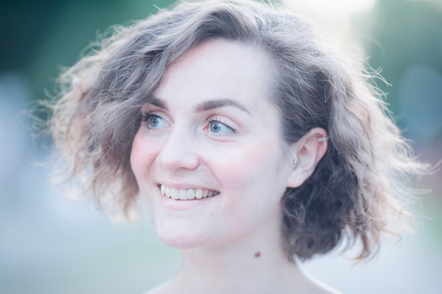 Portret van een jonge mooie vrouw met kort haar die opzij kijkt