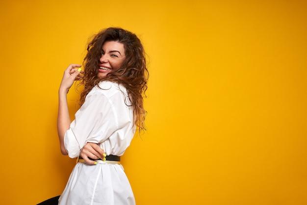 Portret van een jonge mooie vrouw met krullend haar in een wit overhemd