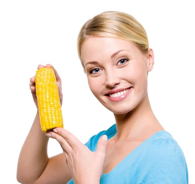 Portret van een jonge mooie vrouw met rauwe maïs - geïsoleerd op wit