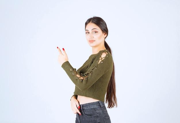 Portret van een jonge mooie vrouw model permanent en opzij wijzend met een wijsvinger.