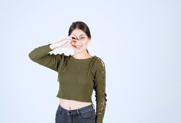 Portret van een jonge mooie vrouw model permanent en poseren over witte muur.
