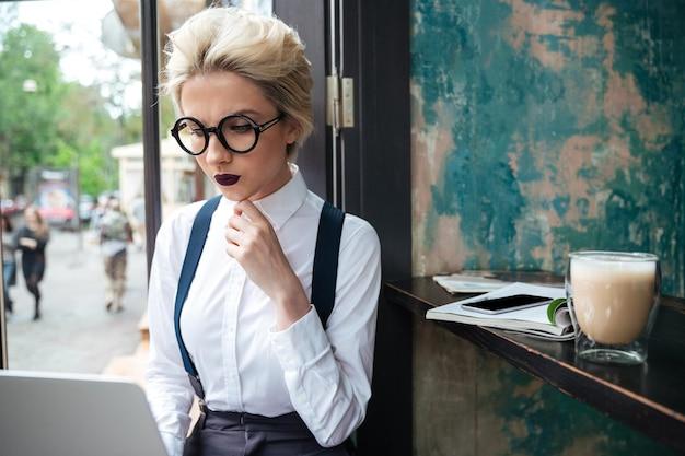 Portret van een jonge, mooie zakenvrouw die van koffie geniet tijdens het werk op een draagbare laptopcomputer