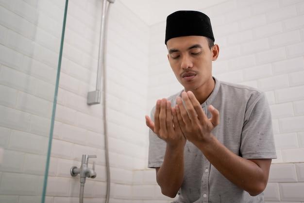 Portret van een jonge moslim man bidden na het uitvoeren van wassing in de badkamer