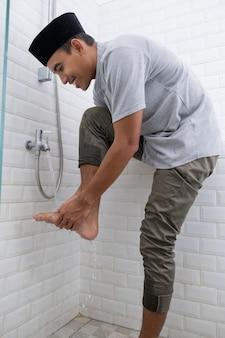 Portret van een jonge moslim man uitvoeren van wassing (wudhu) voor het gebed thuis