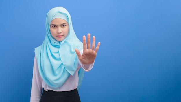 Portret van een jonge moslimvrouw met hijab over blauwe muur