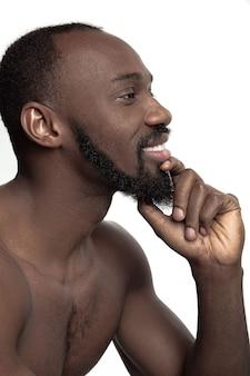 Portret van een jonge naakte gelukkig lachend afrikaanse man in de studio.