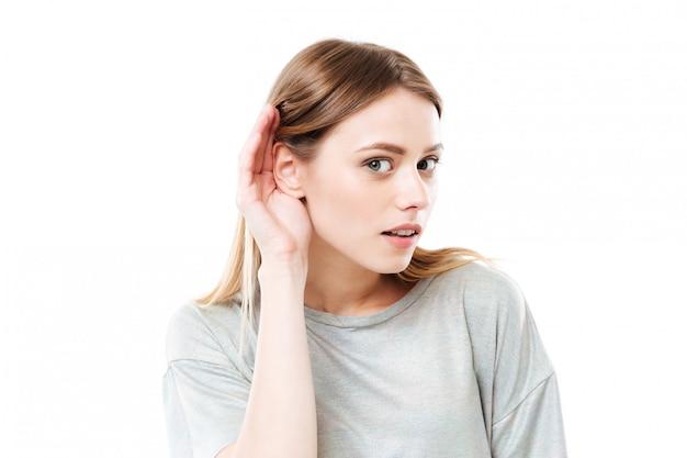 Portret van een jonge nieuwsgierige jonge vrouw die geruchten probeert te horen