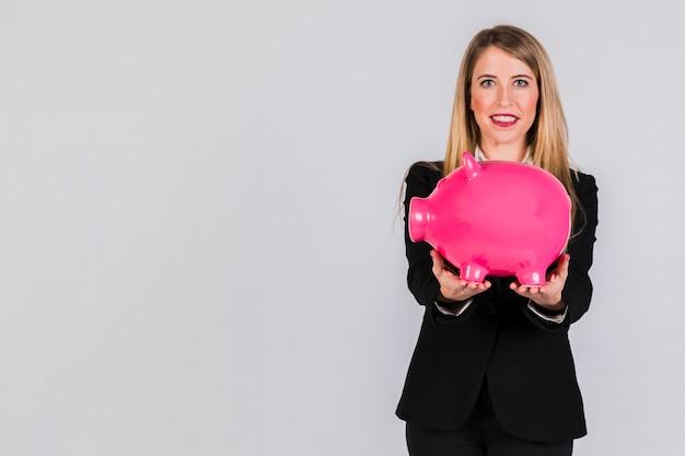 Portret van een jonge onderneemster die grote roze piggybank in hand houden tegen grijze achtergrond
