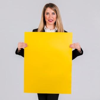 Portret van een jonge onderneemster die het lege gele aanplakbiljet op grijze achtergrond toont