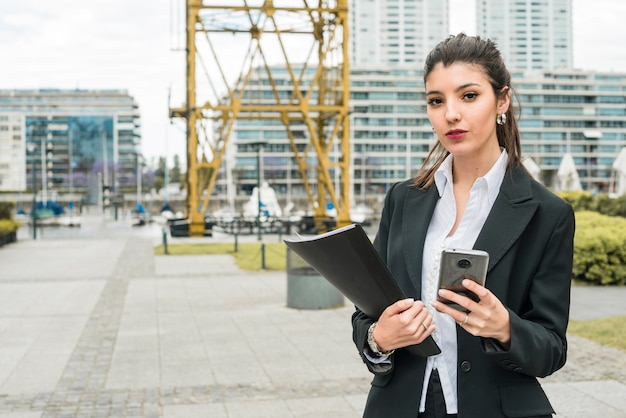 Portret van een jonge onderneemster die slimme telefoon en in hand omslag houdt