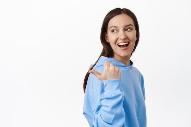 Portret van een jonge openhartige vrouw, gelukkig glimlachend, naar links wijzend en achter haar schouder kijkend naar de verkoopbanner, staande in hoodie tegen de witte muur.