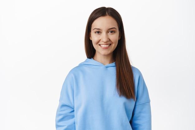 Portret van een jonge openhartige vrouw in blauwe hoodie, natuurlijk donker haar, lachende witte tanden, er gelukkig en zelfverzekerd uitziend, staande tegen de witte muur.