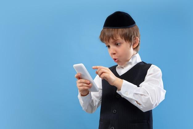Portret van een jonge orthodoxe joodse jongen die op blauwe muur wordt geïsoleerd die het pascha ontmoet