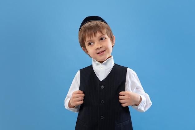 Portret van een jonge orthodoxe joodse jongen die op blauwe studio wordt geïsoleerd