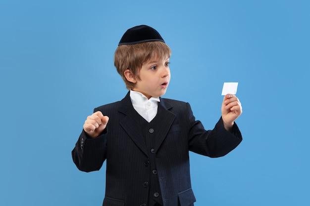 Portret van een jonge orthodoxe joodse jongen geïsoleerd op blauwe studio