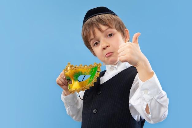 Portret van een jonge orthodoxe joodse jongen met carnaval masker geïsoleerd op blauwe studio