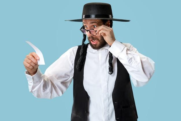 Portret van een jonge orthodoxe joodse man met een gokje bij studio. vakantie, feest, jodendom, wedden concept.