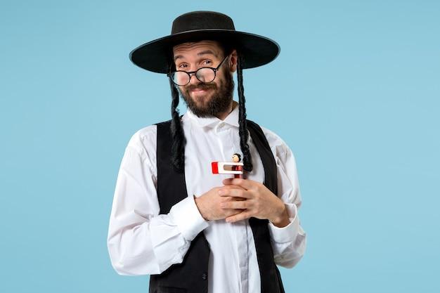 Portret van een jonge orthodoxe joodse man met houten grager-ratel tijdens festival purim.