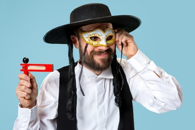 Portret van een jonge orthodoxe joodse man met houten grager-ratel tijdens festival